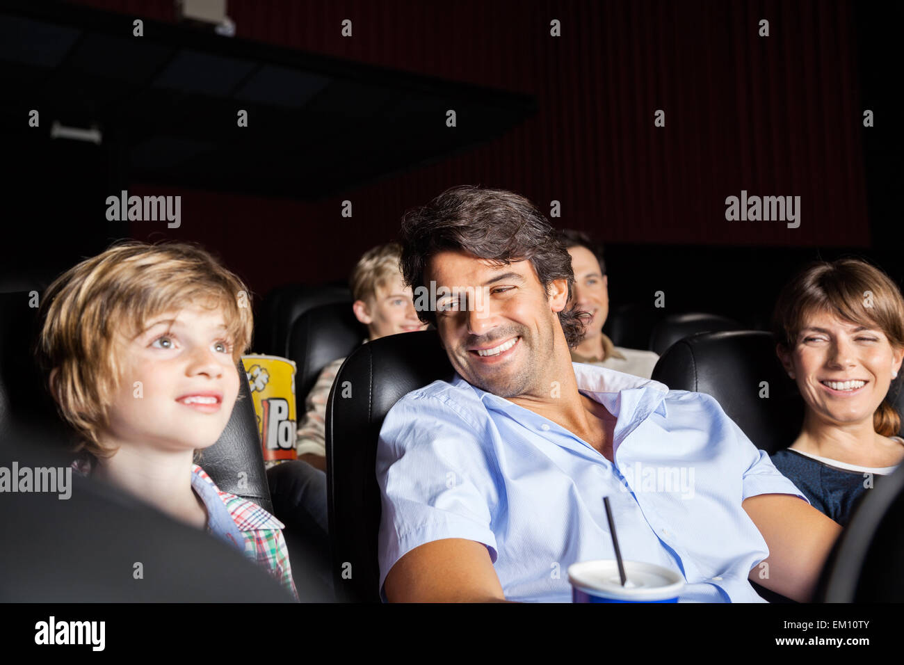 Happy Family Watching Movie In Theater - Stock Image
