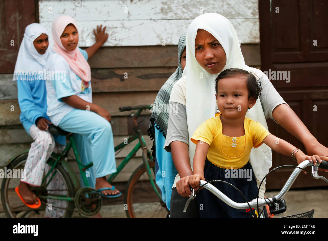 Muslim girls in headscarves play on bicycles; Banda Aceh, Aceh Province, Sumatra, Indonesia Stock Photo
