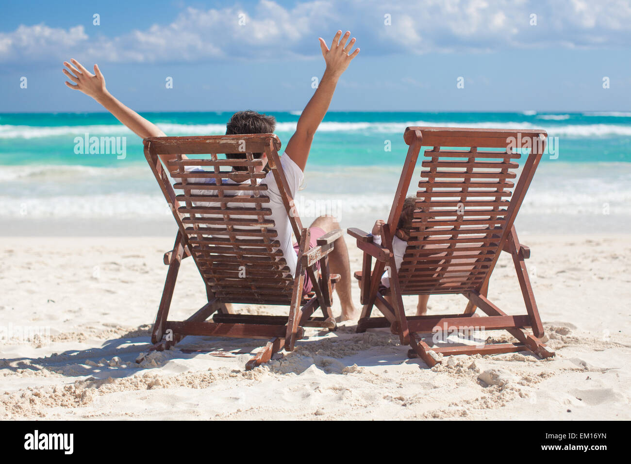 young father with daughter in beach chairs raised their hands up ...