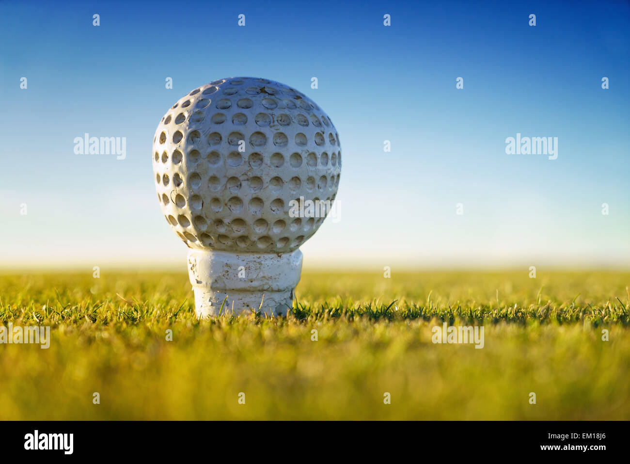 A large golf ball marker on the tee of a golf course in Scotland. - Stock Image