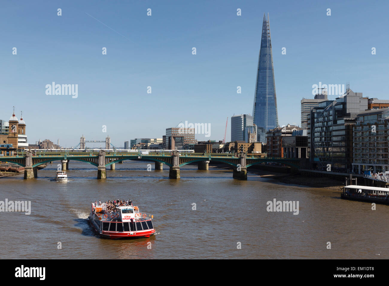 City cruises boat trip on the River Thames, London in front of the Shard building and Southwark Bridge - Stock Image