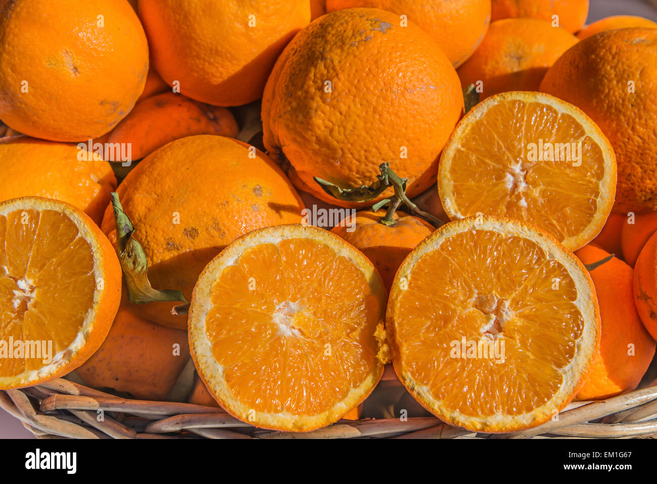 Fresh local oranges on display with two cut through displaying the juicy cross section - Stock Image