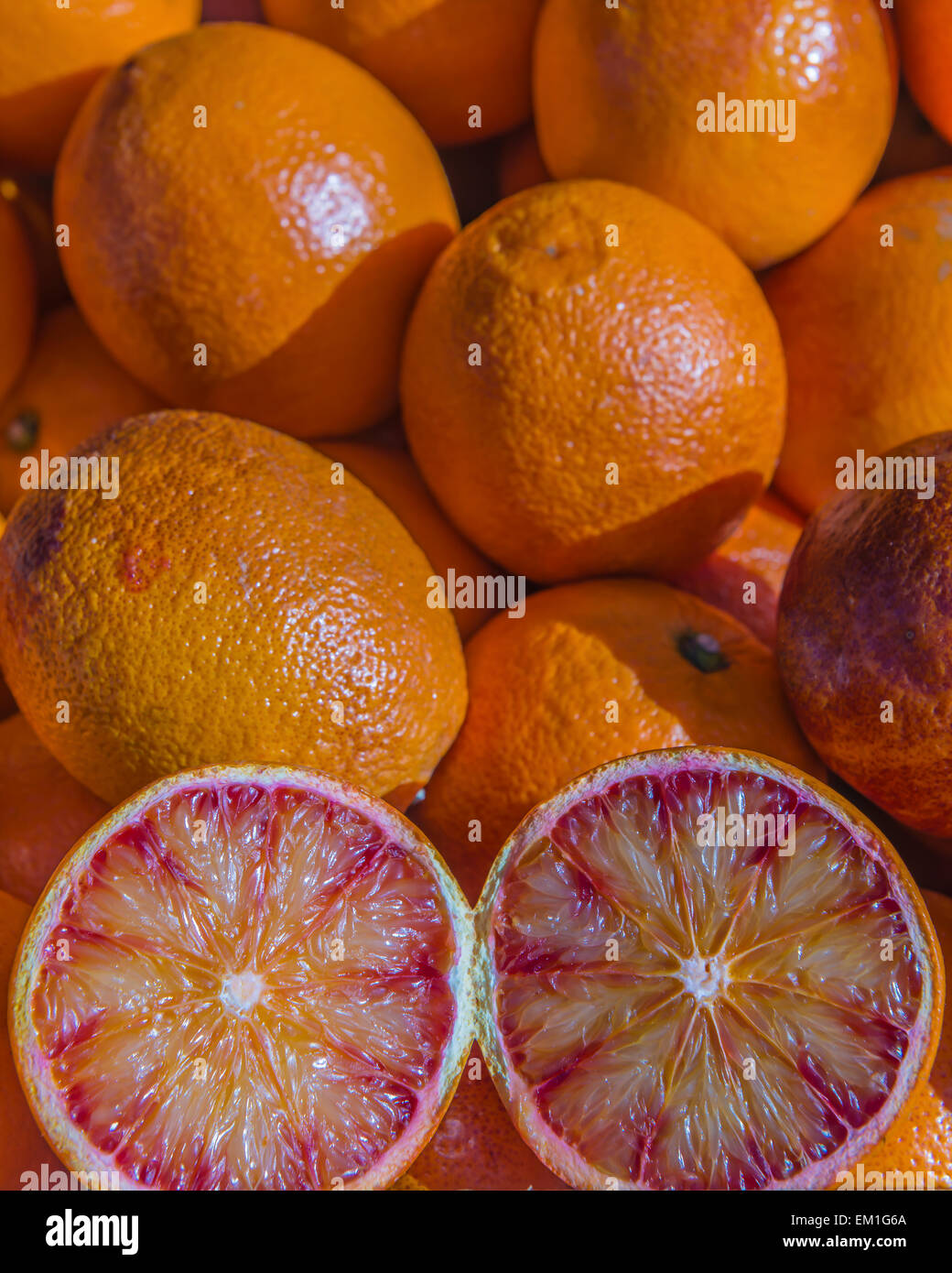 Fresh local blood oranges on display with one cut through displaying the juicy cross section - Stock Image
