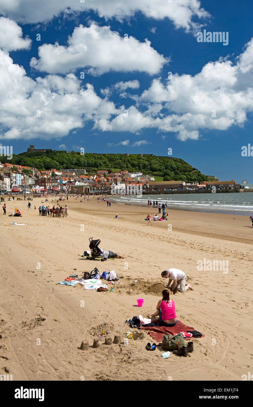 UK, England, Yorkshire, Scarborough, visitors relaxing in sunshine on South Sands - Stock Image