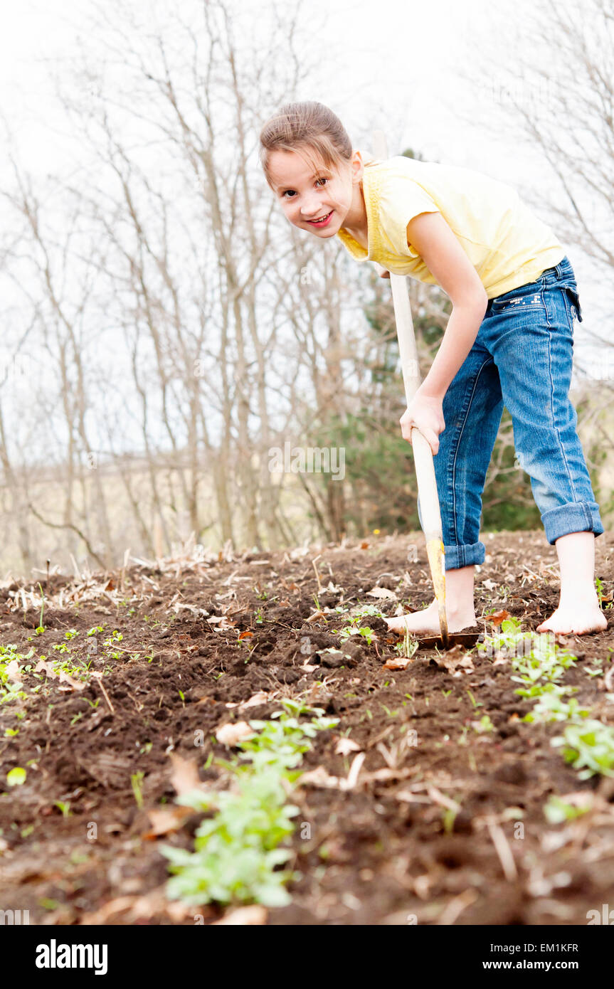 Girl helping to hoe the garden - Stock Image