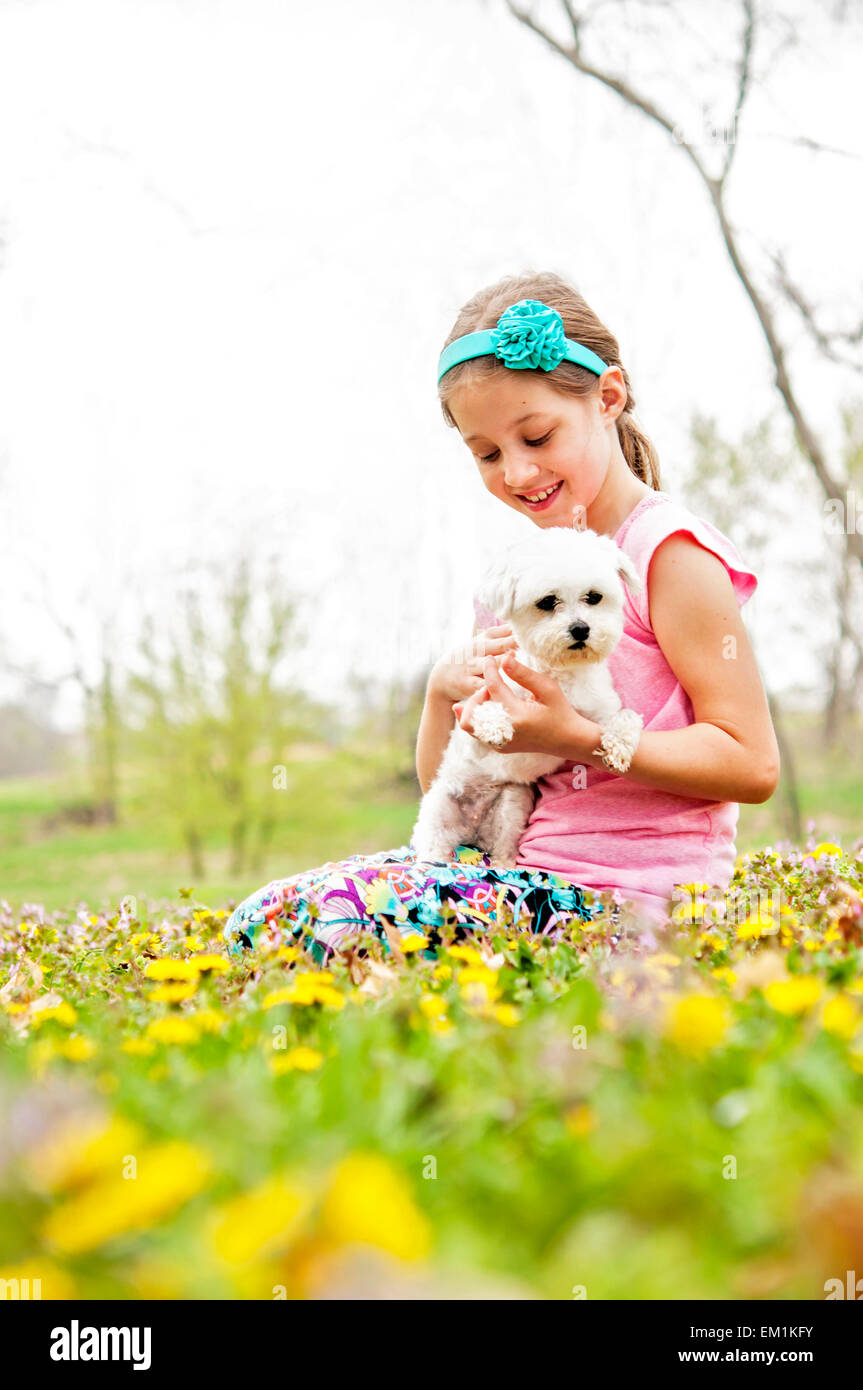 Girl pets dog in wildflower meadow - Stock Image