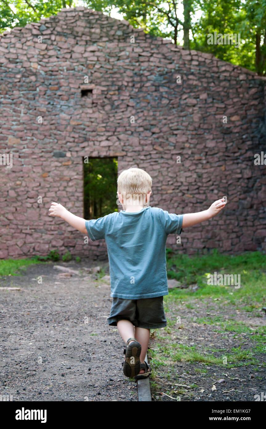 boy balances on railroad track - Stock Image
