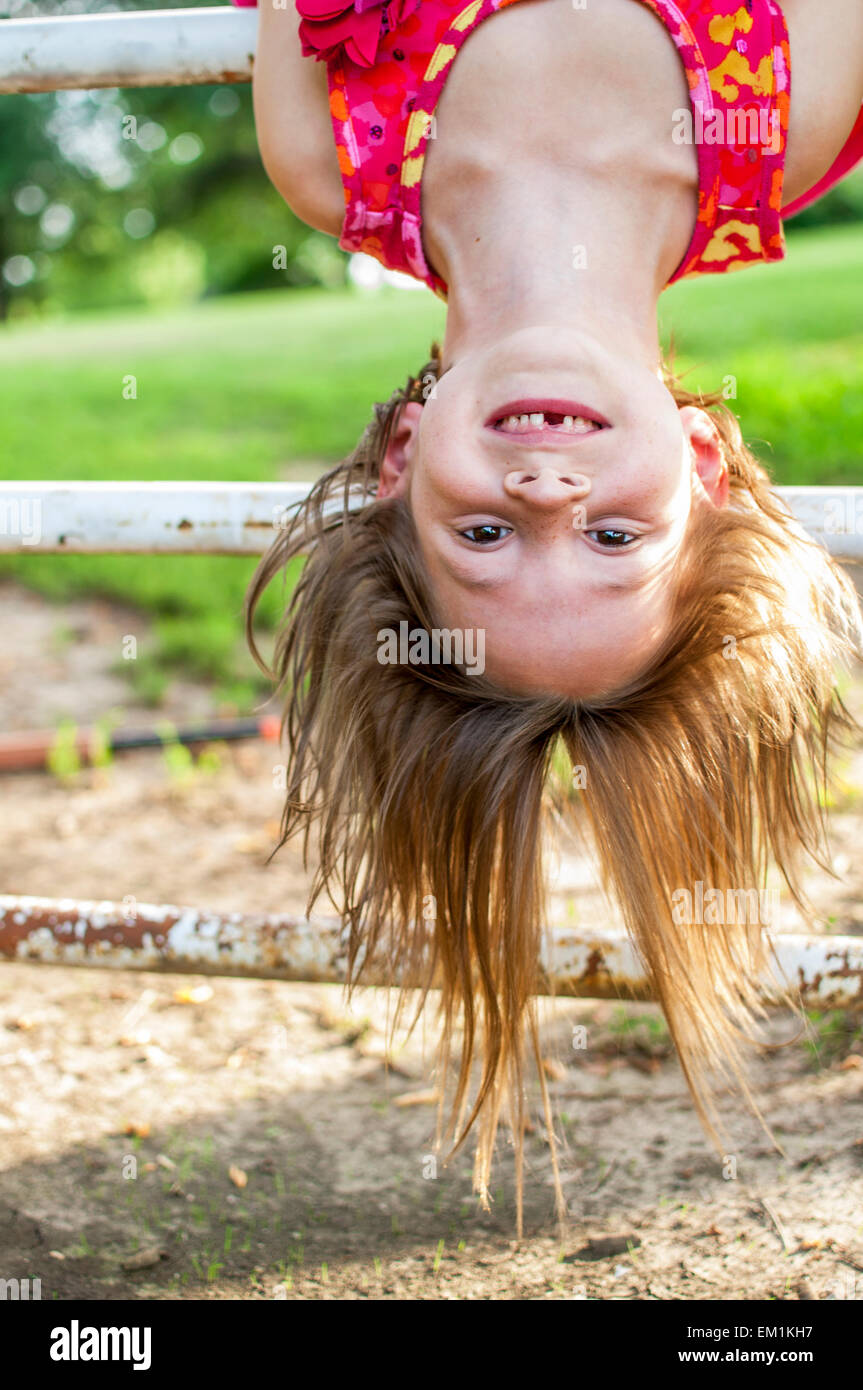 girl missing teeth upside down - Stock Image