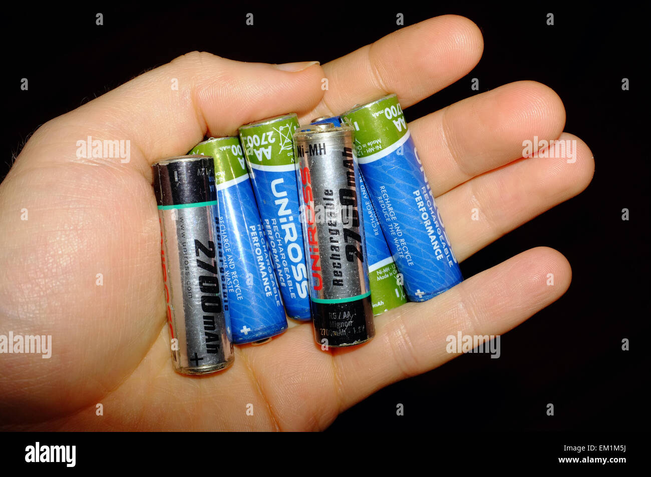 A white hand holding a AA rechargeable batteries against a black background. - Stock Image