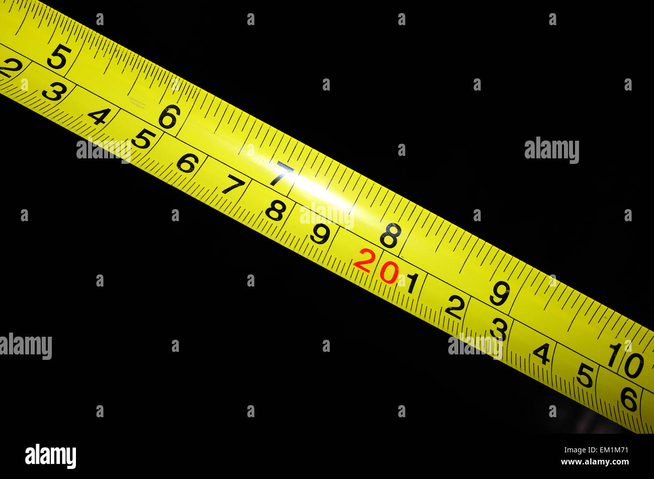 A yellow tape measure held against a black background. - Stock Image