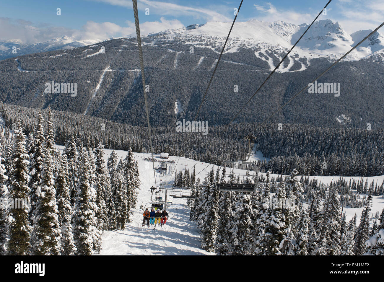 Skiers Riding A Chairlift At A Ski Resort; Whistler British Columbia Canada - Stock Image