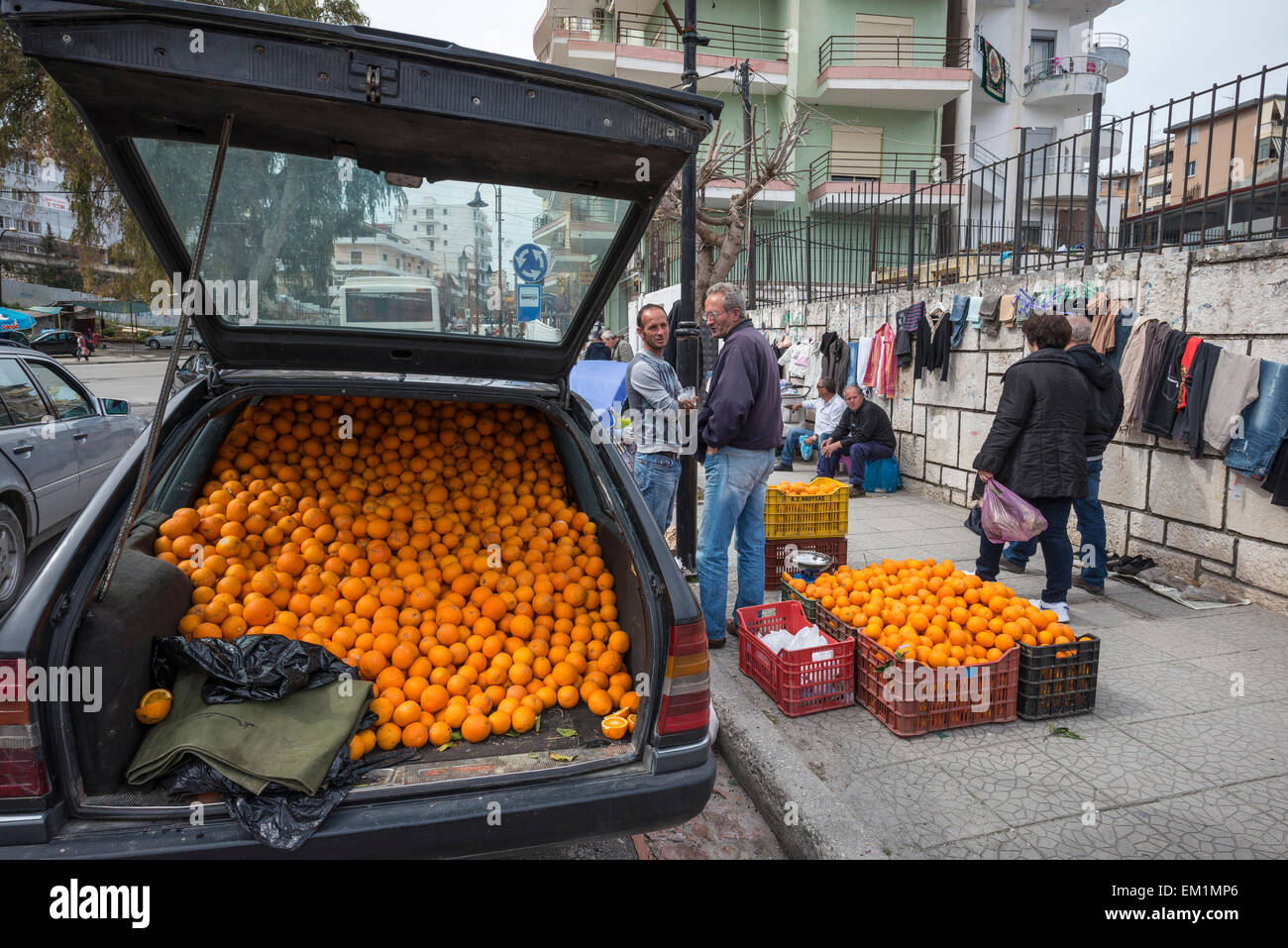 Selling oranges from the back of a Mercedes at a street market in Saranda, Southern Albania. - Stock Image