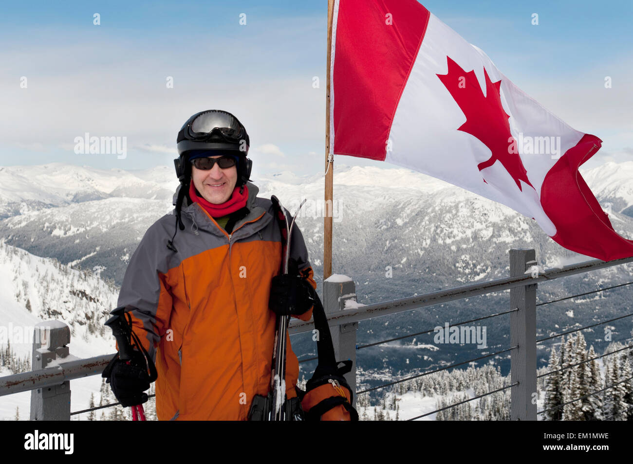 A Skier Stands Beside The Canadian Flag On A Balcony At A Ski Resort; Whistler British Columbia Canada - Stock Image
