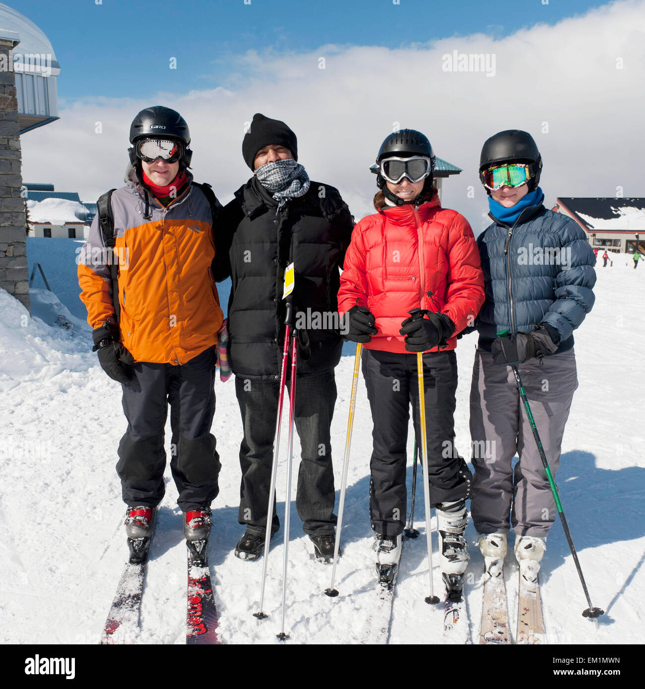 Four Skiers Ready To Go At A Ski Resort; Whistler British Columbia Canada - Stock Image
