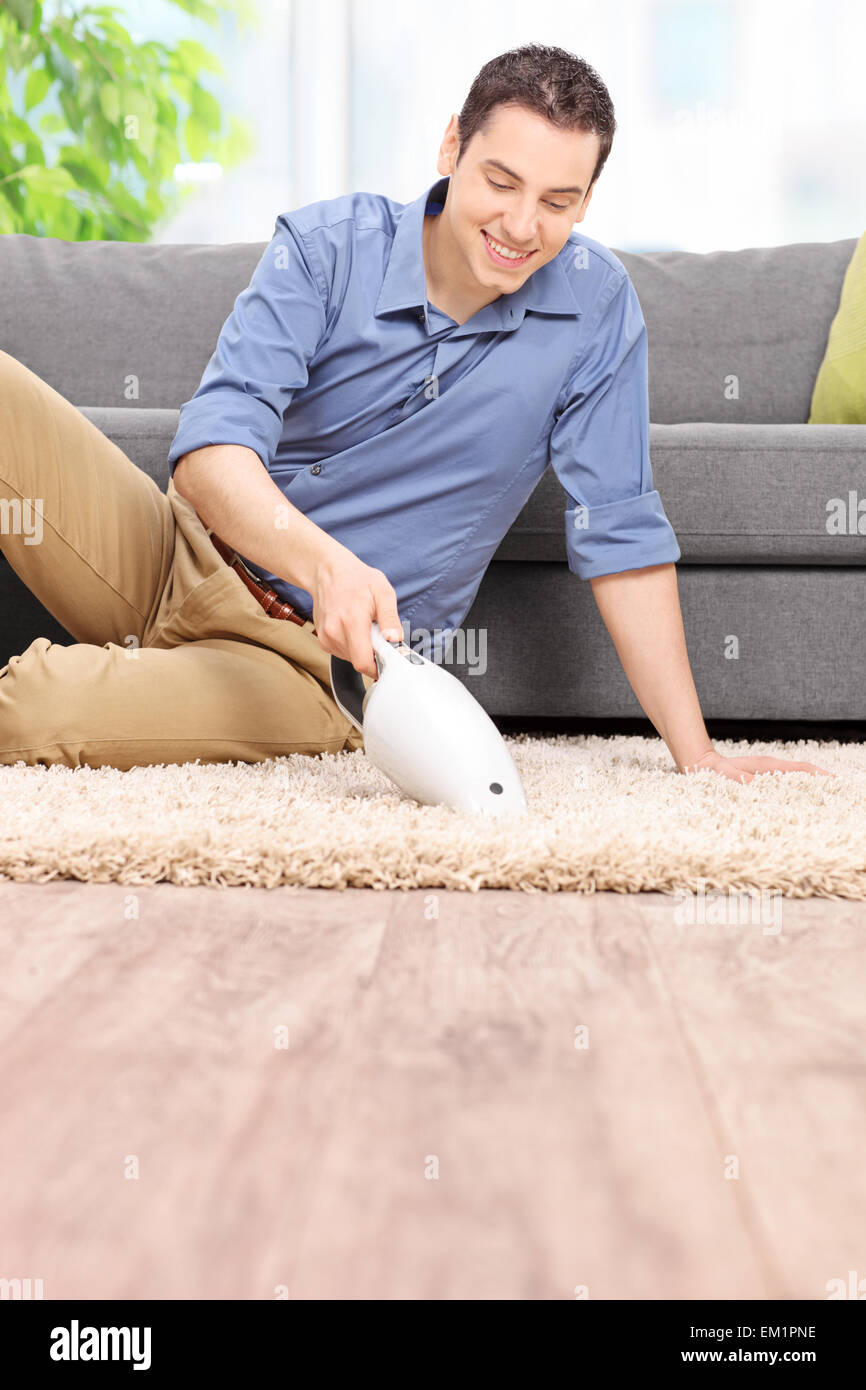 Vertical shot of a young man holding a handheld vacuum cleaner and cleaning a carpet at home Stock Photo