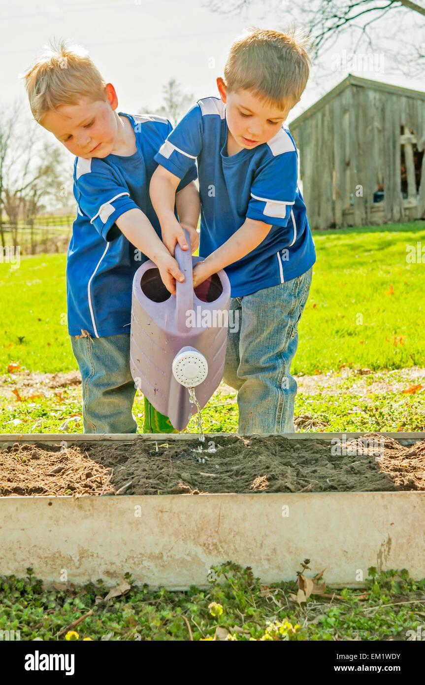 boys watering garden - Stock Image