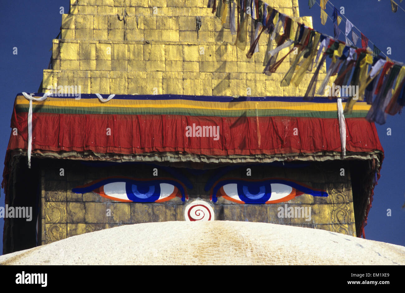 Nepal, Close-up of painted eyes on Boudhanath Stupa and colorful streaming flags; Kathmandu - Stock Image