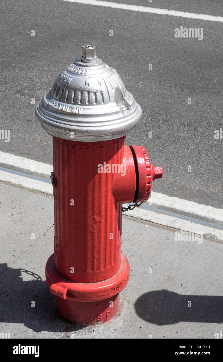 A red painted fire hydrant on the sidewalk on a street in New York City - Stock Image