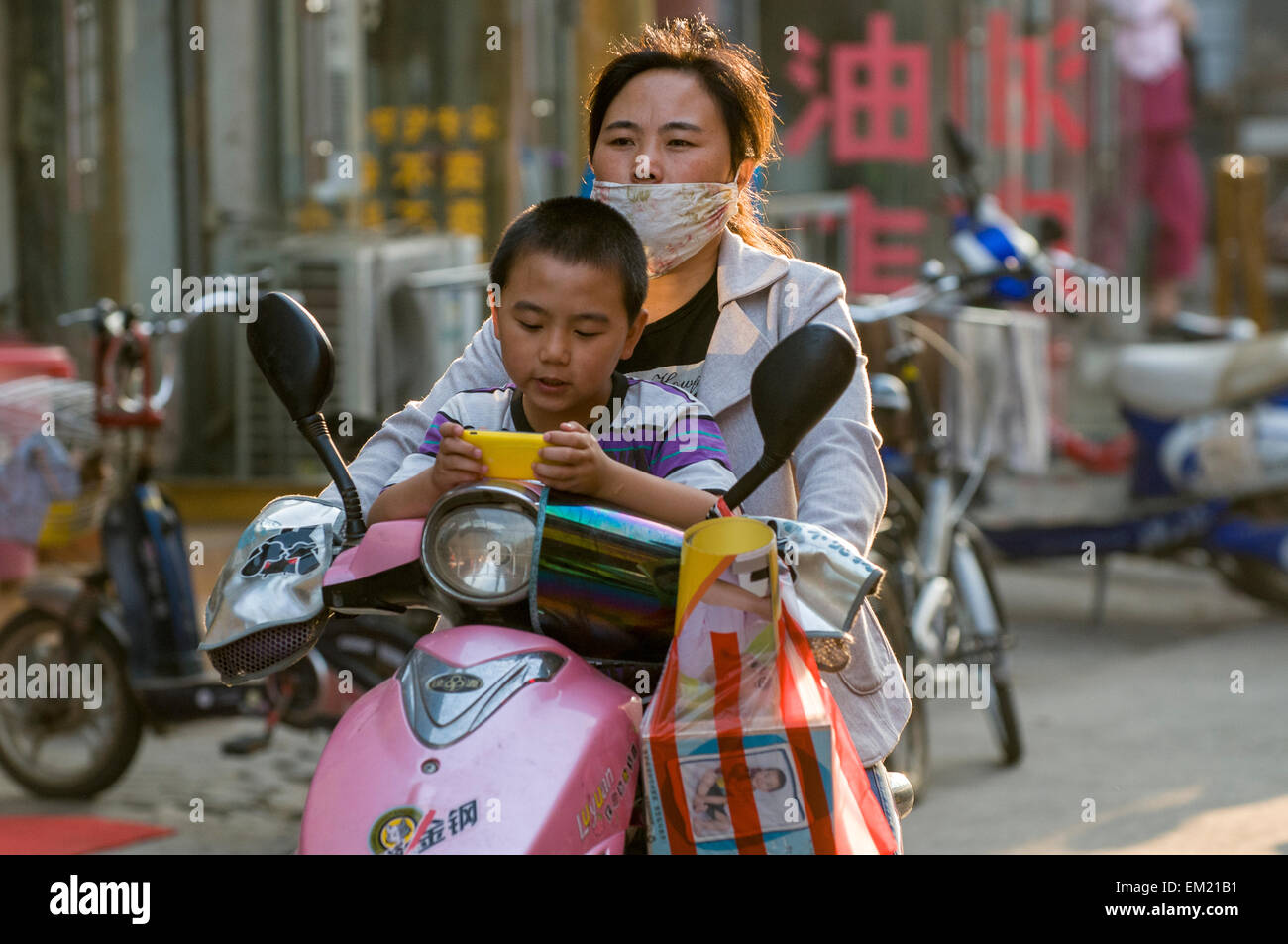 Son plays video game whle mother wearing facemask against pollution drives scooter, Lianyungang, Jiansu Province, - Stock Image