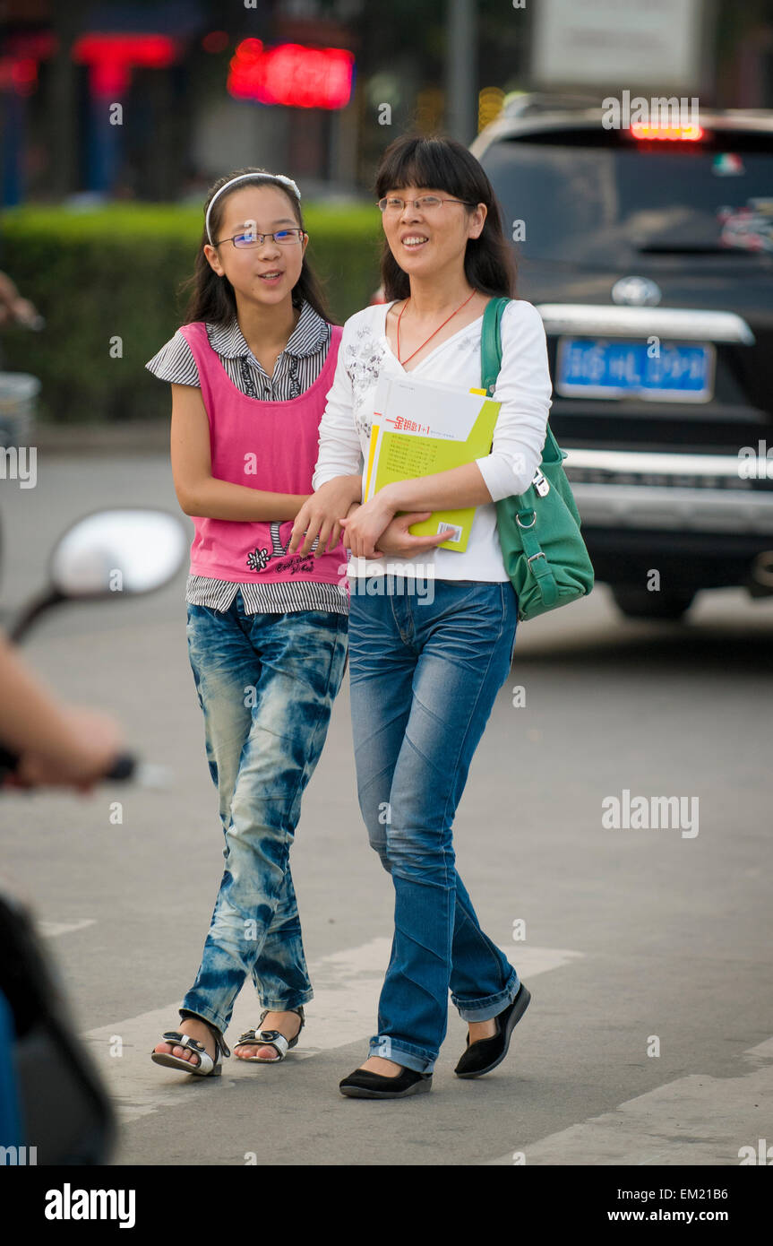 Teen daughter strolls arm in arm with mother, Lianyungang, Jiansu Province, China. - Stock Image