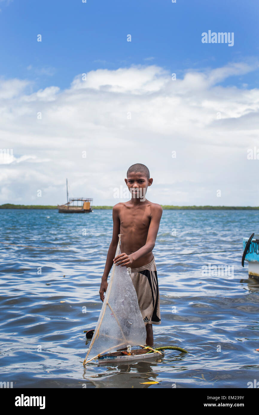 LAMU, KENYA, AFRICA. A boy in bathing suit stands in shallow water holding a small toy sailboat. - Stock Image