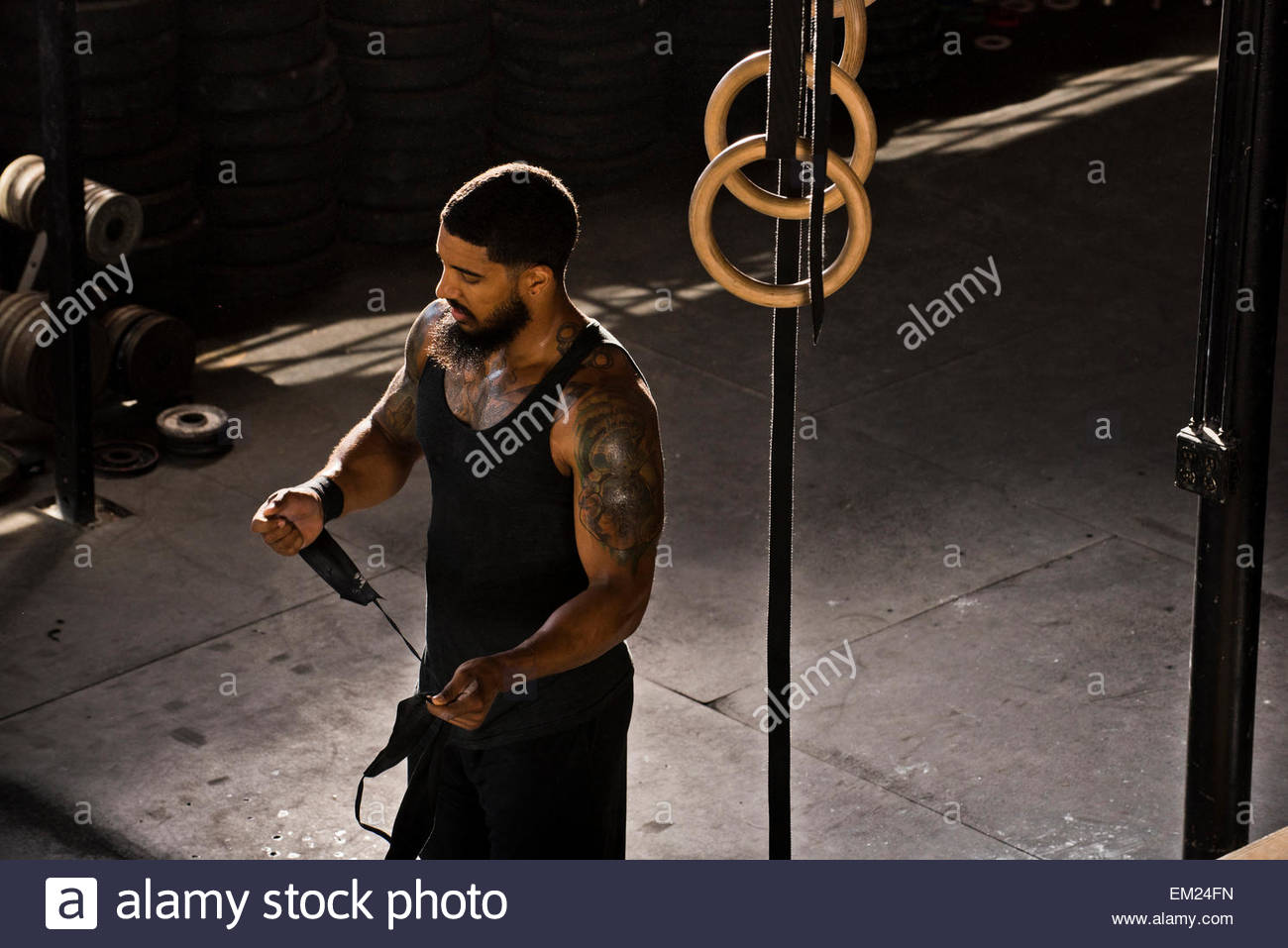 A crossfit athlete taking off his wrist wraps. - Stock Image
