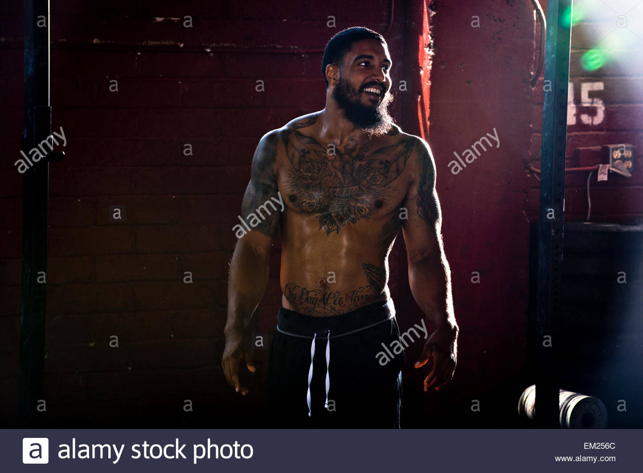 A crossfit athlete laughs after a workout. - Stock Image