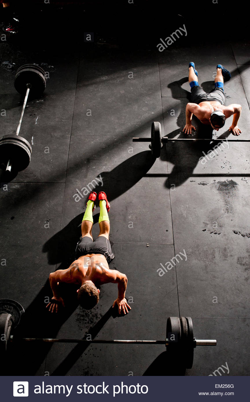 Two crossfit athletes perform burpees. - Stock Image