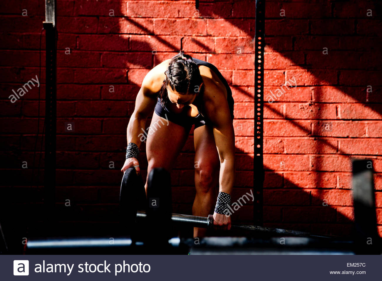 A young man adjusts bumper plate on barbell in San Diego crossfit gym. - Stock Image