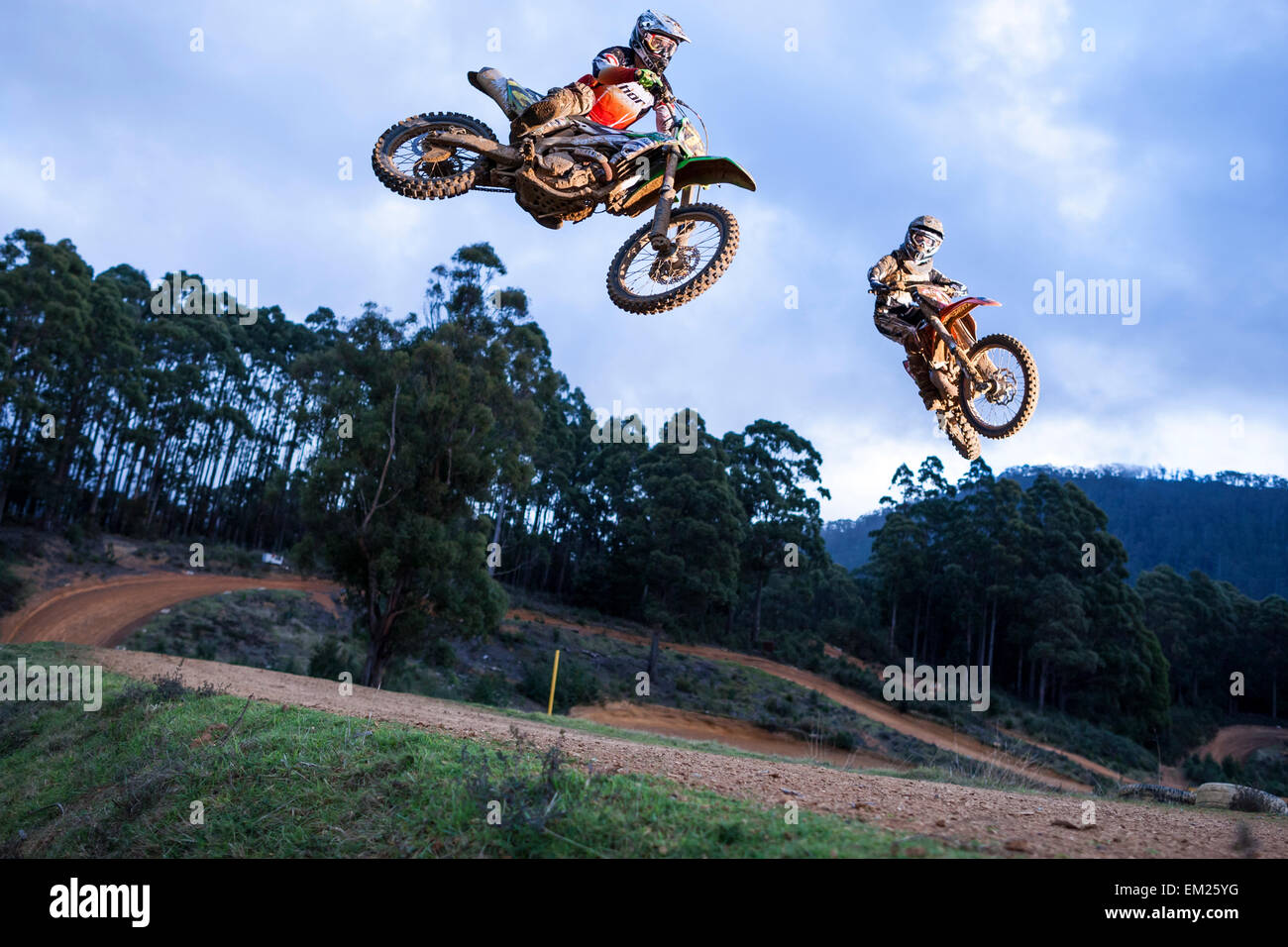 Two dirt bike racers jumping tabletop. - Stock Image