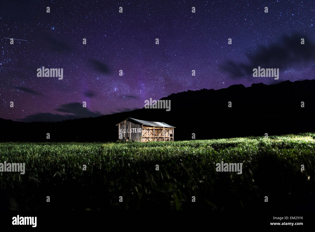 Country barn with Aurora Australis behind mountain - Stock Image