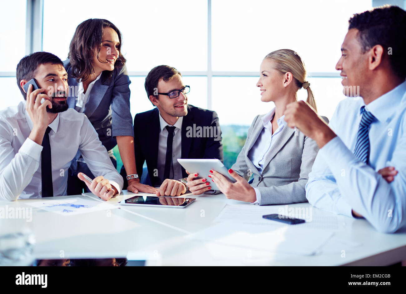 Happy co-workers discussing ideas in office - Stock Image