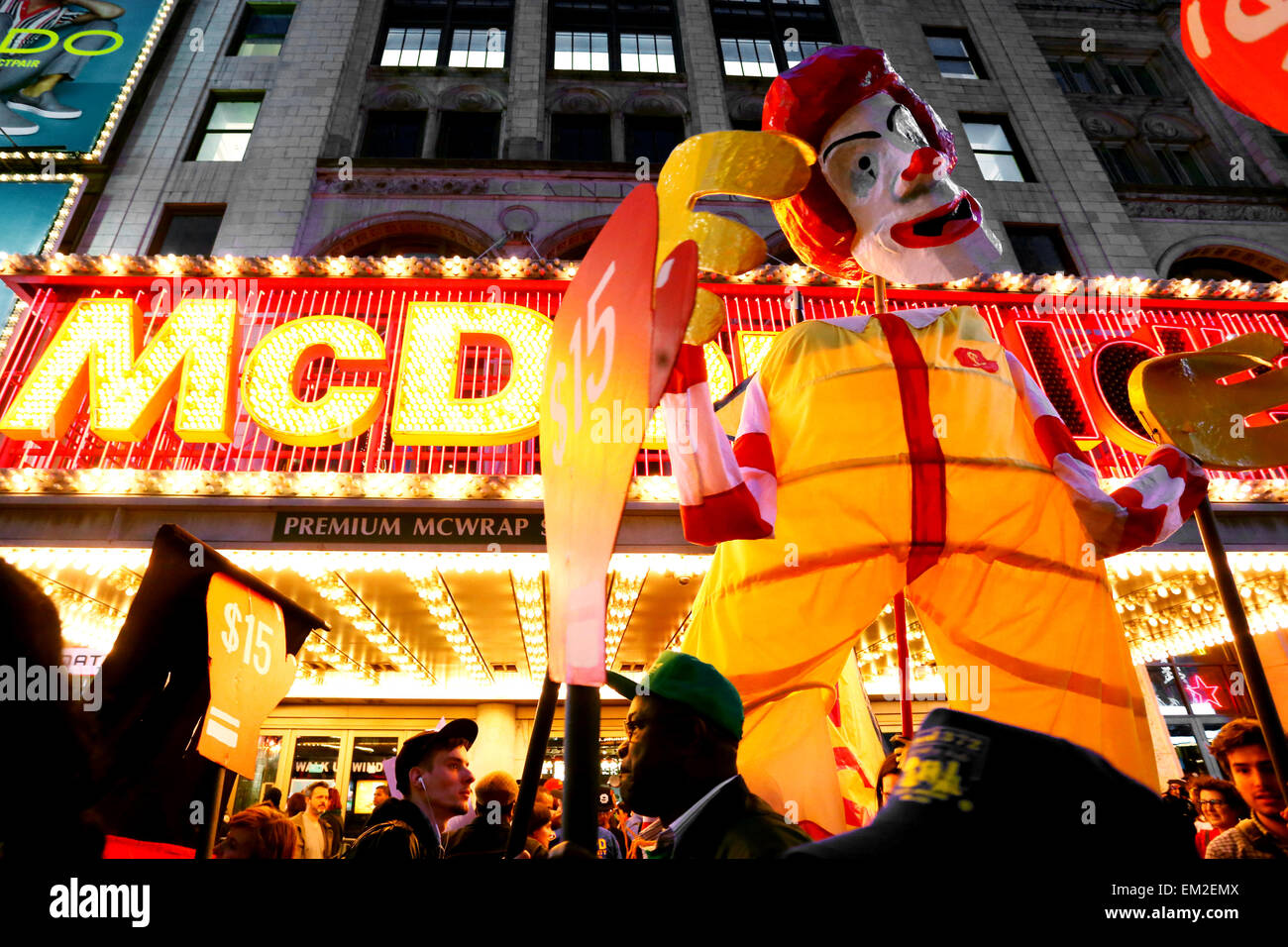 Activists parade a large 'Ronnie McDonald' puppet in front of McDonalds at a Fight for $15 demonstration - Stock Image