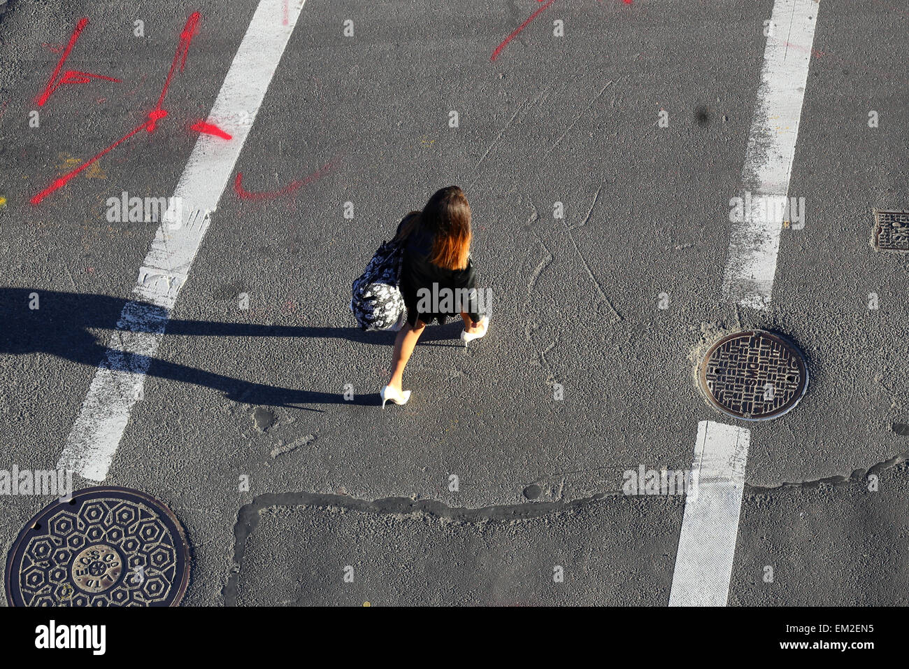 A person in a crosswalk. - Stock Image