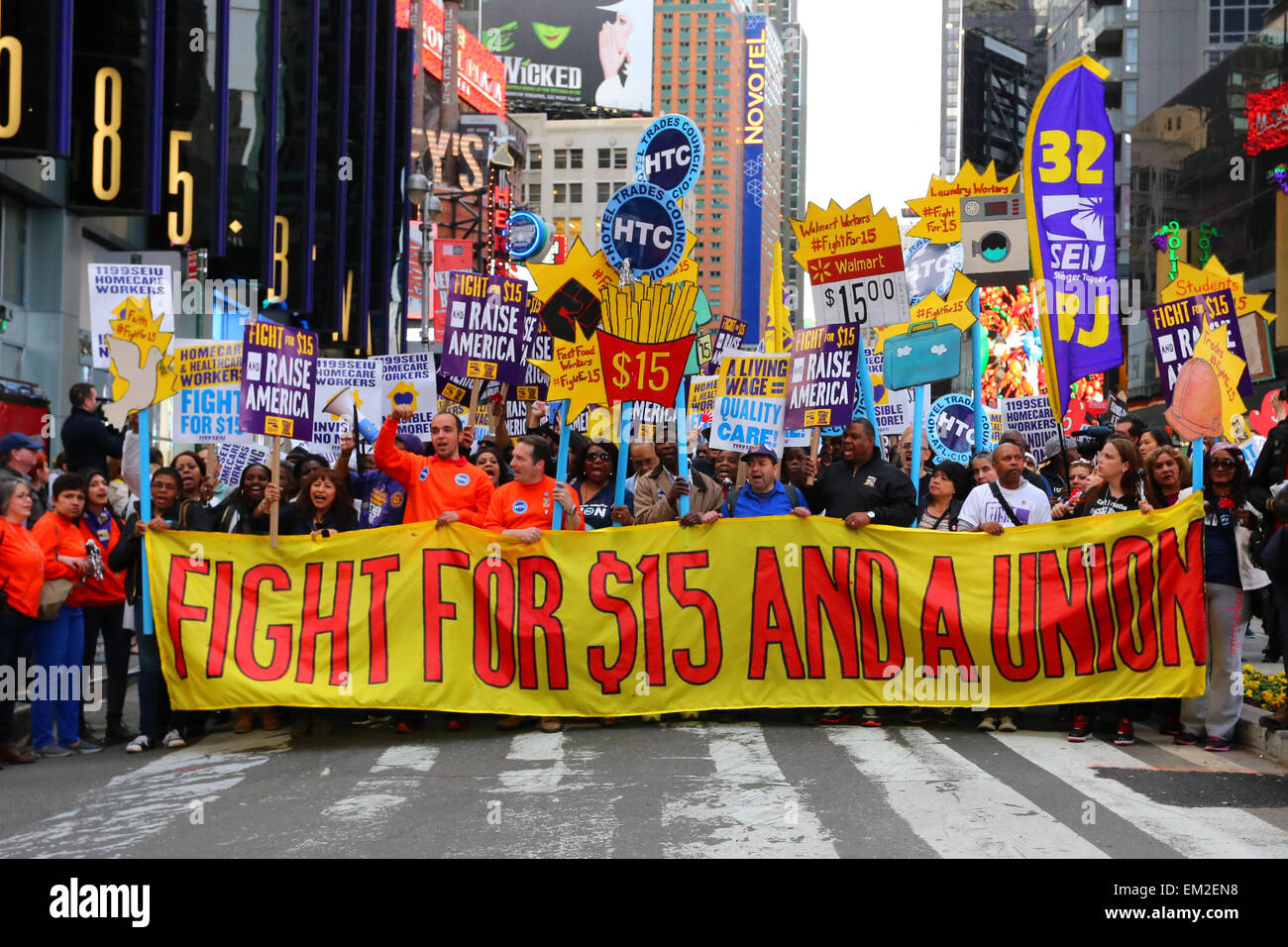 Activists in Times Square unfurl a large banner 'Fight for $15 And A Union' - Stock Image