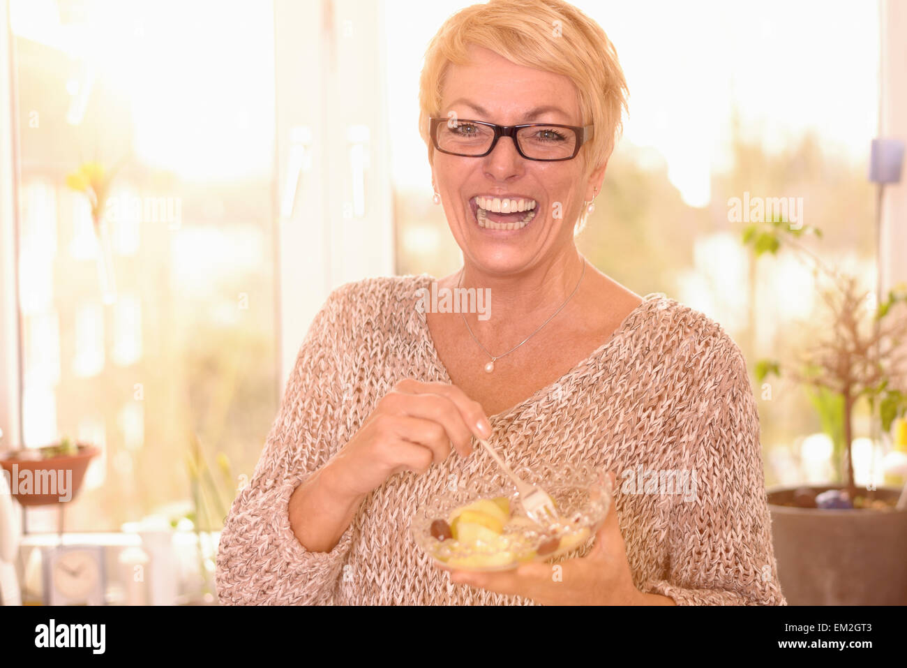 Vivacious attractive middle-aged woman wearing glasses eating a healthy bowl of fruit salad rich in vitamins - Stock Image