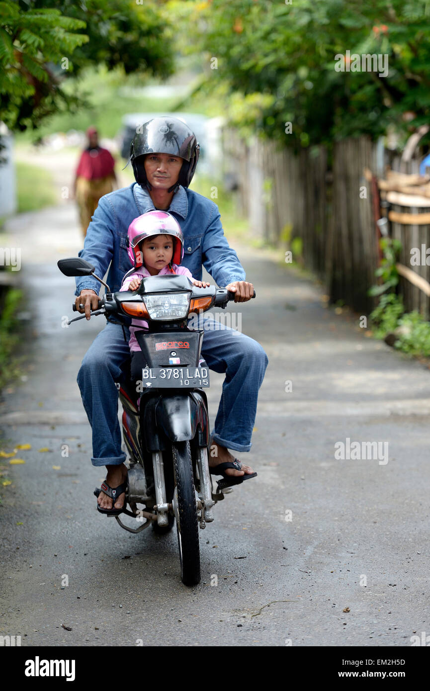 Man with child on a motorcycle, Gampong Nusa village, Aceh, Indonesia - Stock Image