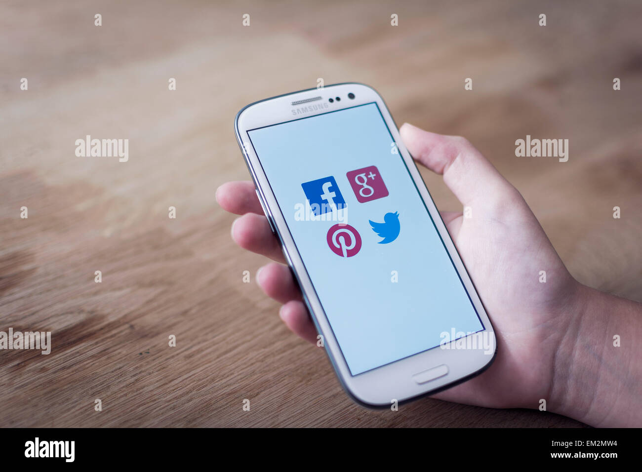 Children's hand holding mobile phone with logo's of popular network sites. - Stock Image