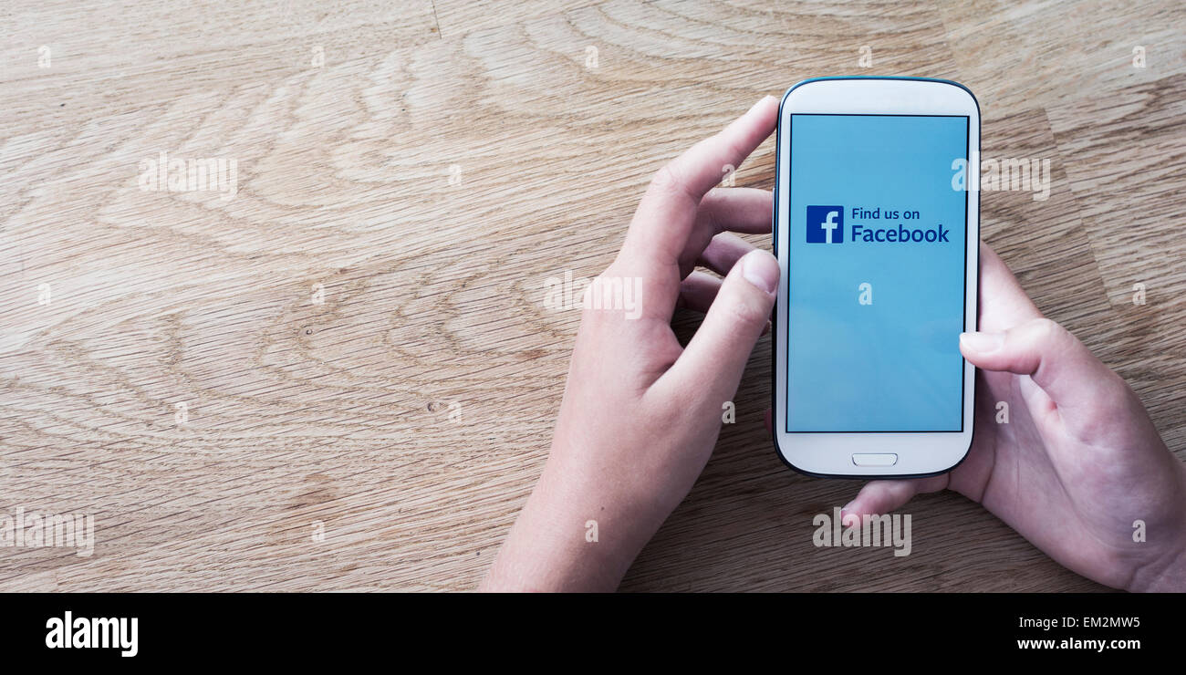 Hands holding mobile phone with facebook screen or logo Stock Photo