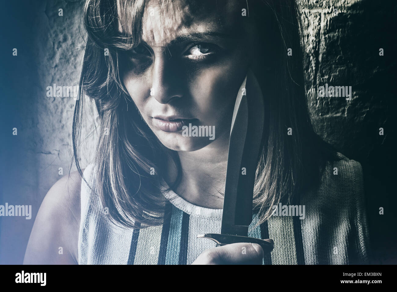 Angry woman holding a dagger - Stock Image
