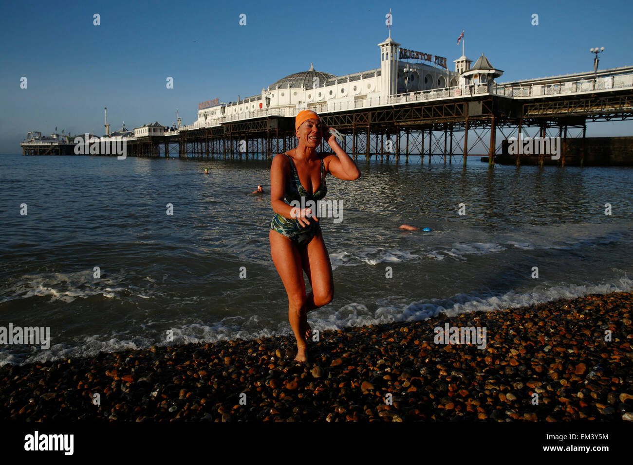 A member of Brighton Swimming Club gets out of the sea after a morning swim Brighton Pier in East Sussex Britain - Stock Image