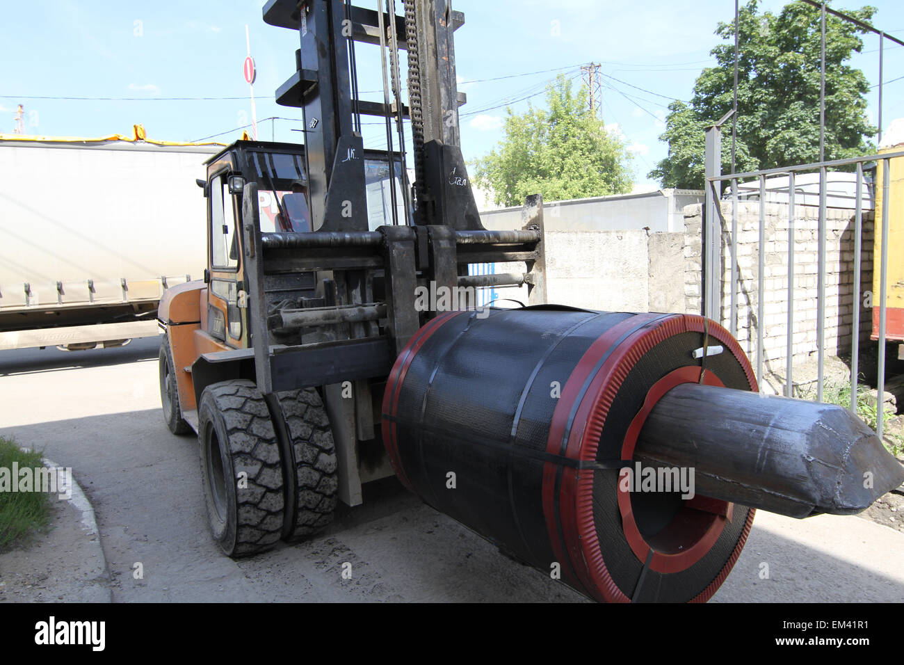 loader moves the roll of steel with the help of special equipment - Stock Image