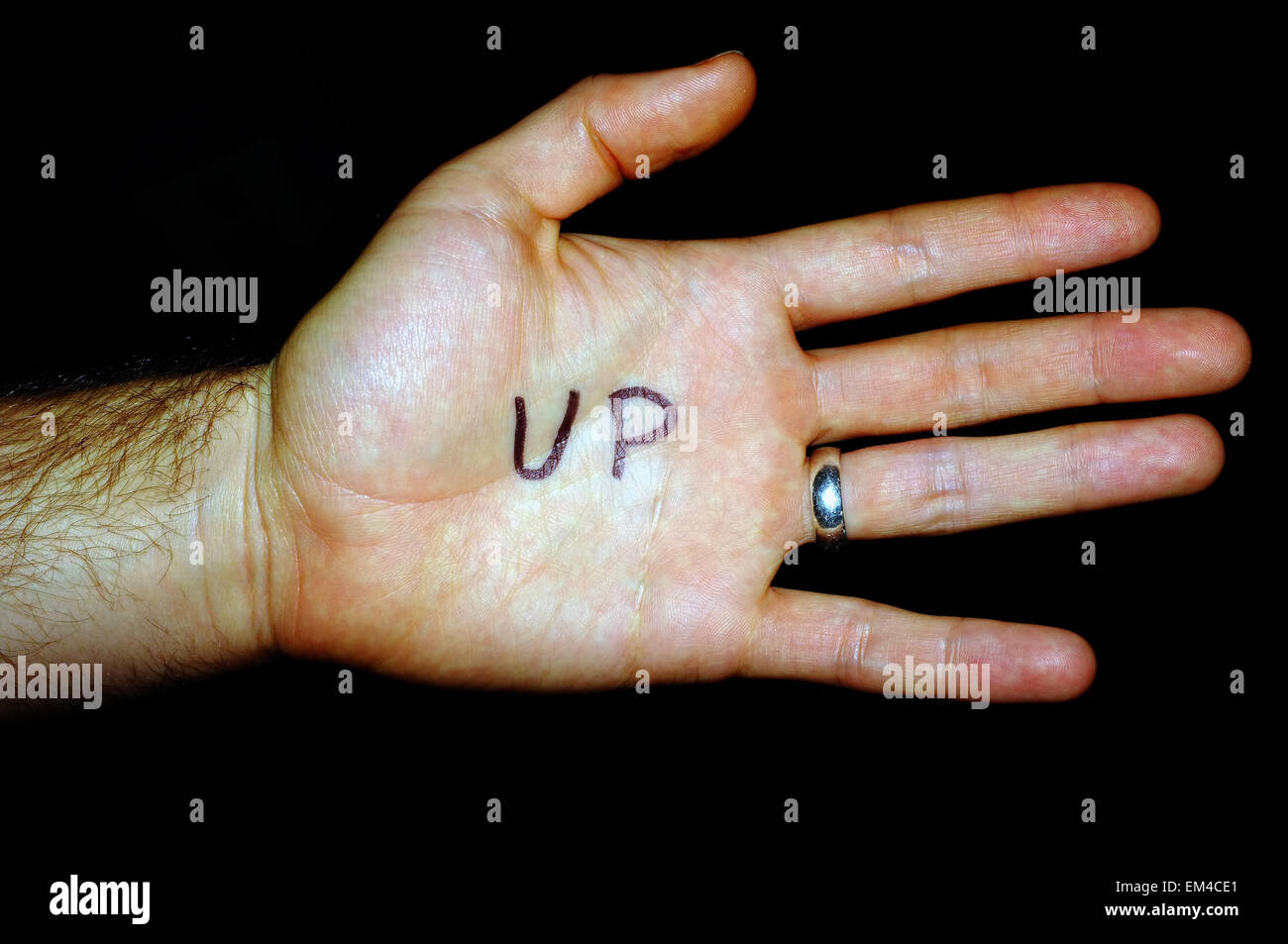 Up written on a white man's hand photographed against a black background. - Stock Image
