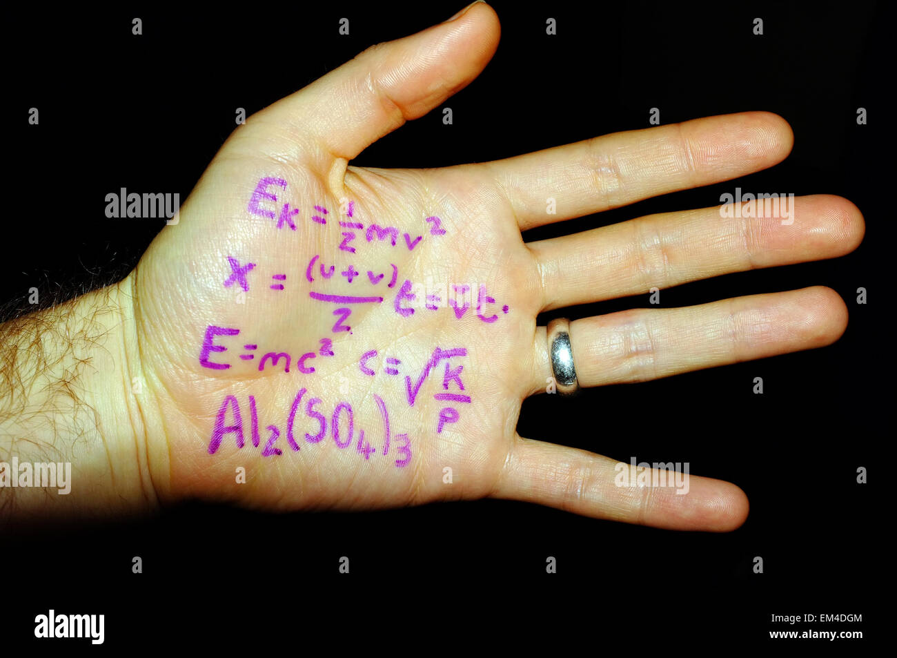 Physics formulas written on a white man's hand photographed against a black background. - Stock Image