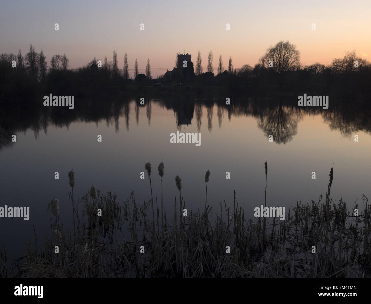 The parish church of Saint Wilfrid in South Muskham Nottinghamshire reflected in the waters of a nearby lake. - Stock Image