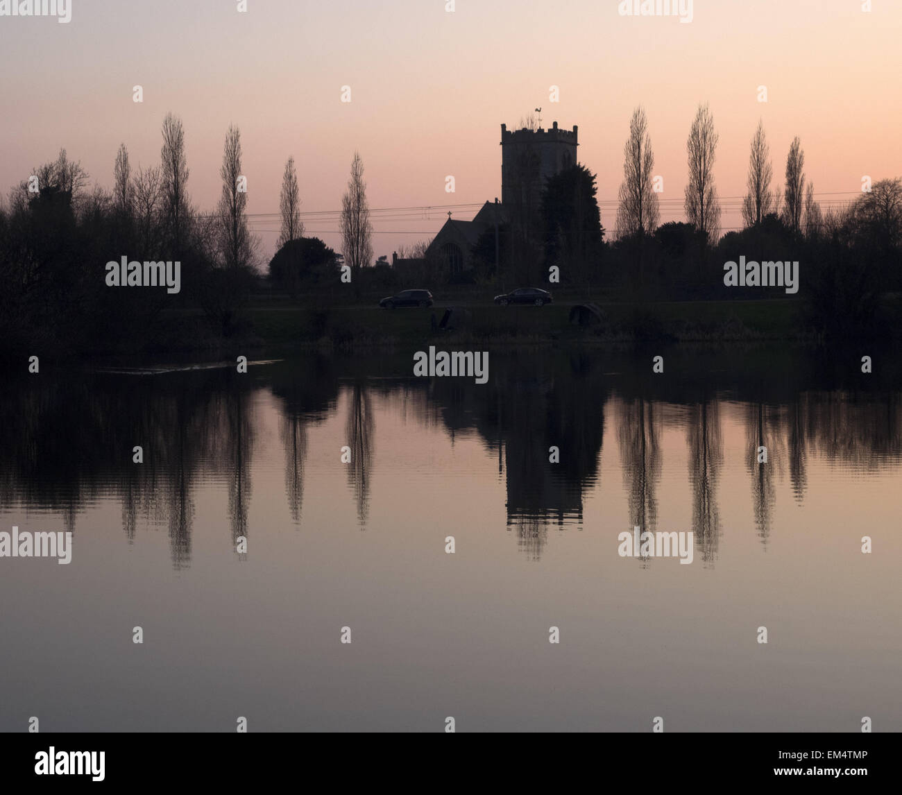 The church of Saint Wilfrid in South Muskham Nottinghamshire reflected in the waters of a lake nearby. - Stock Image