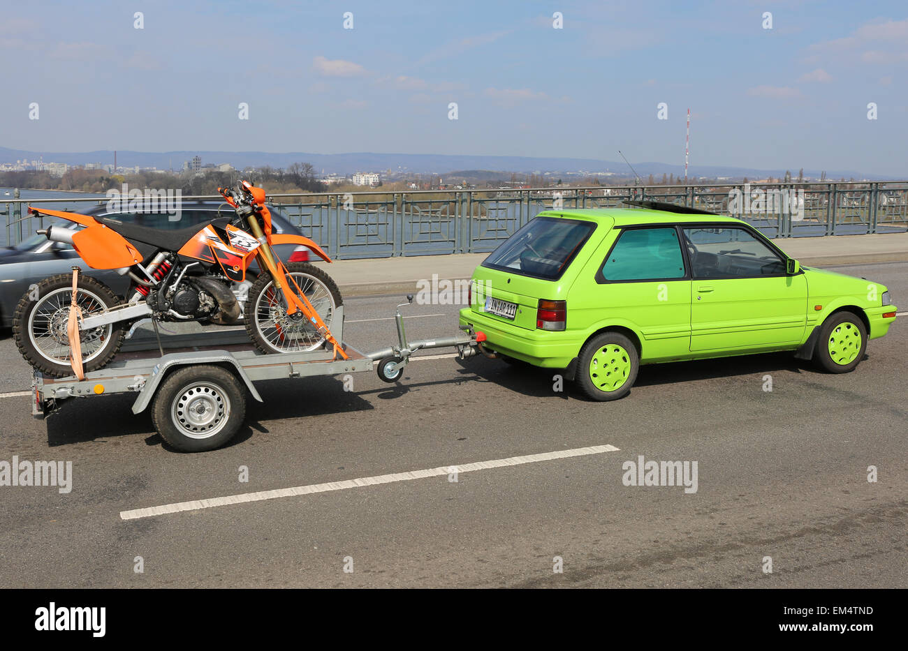Green Car with Orange Dirt Bike on Theodor Heuss Bridge - Stock Image
