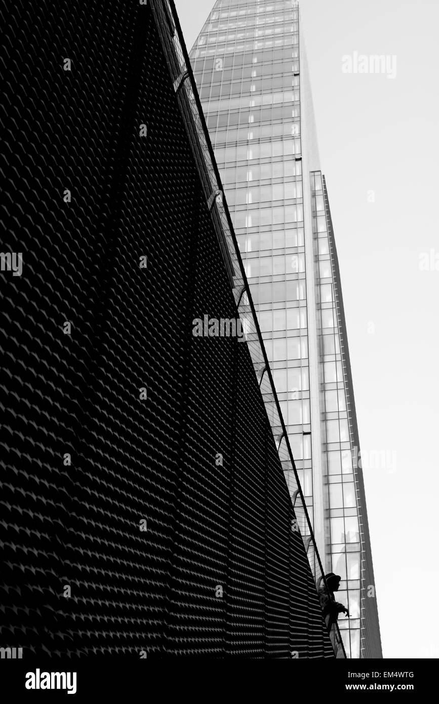 Person looking out from the railing of a skyscraper - Stock Image