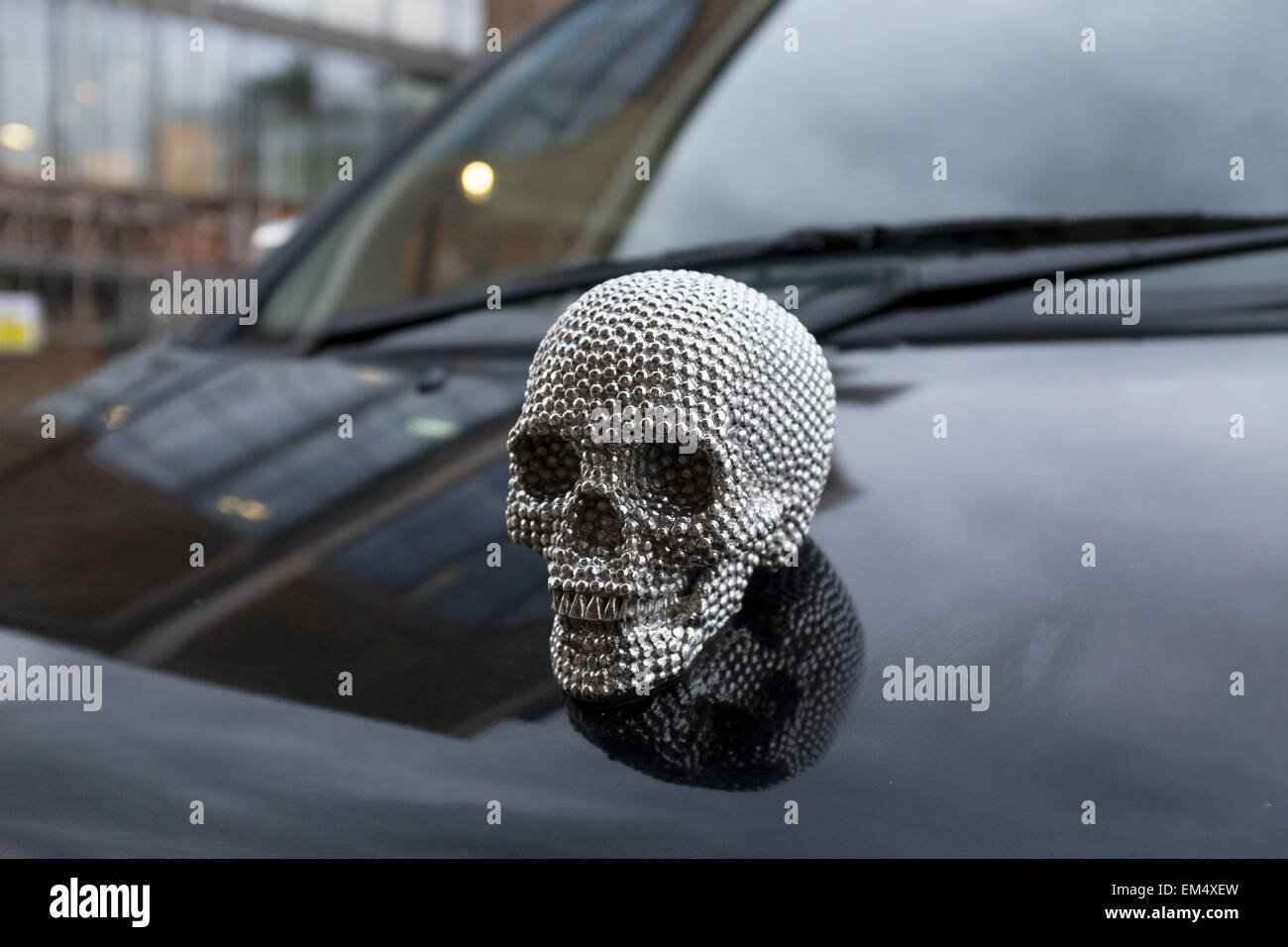 Metallic skull bonnet badge on the hood of a taxi. This small human head is styled on the Damien Hirst diamond skull, Stock Photo