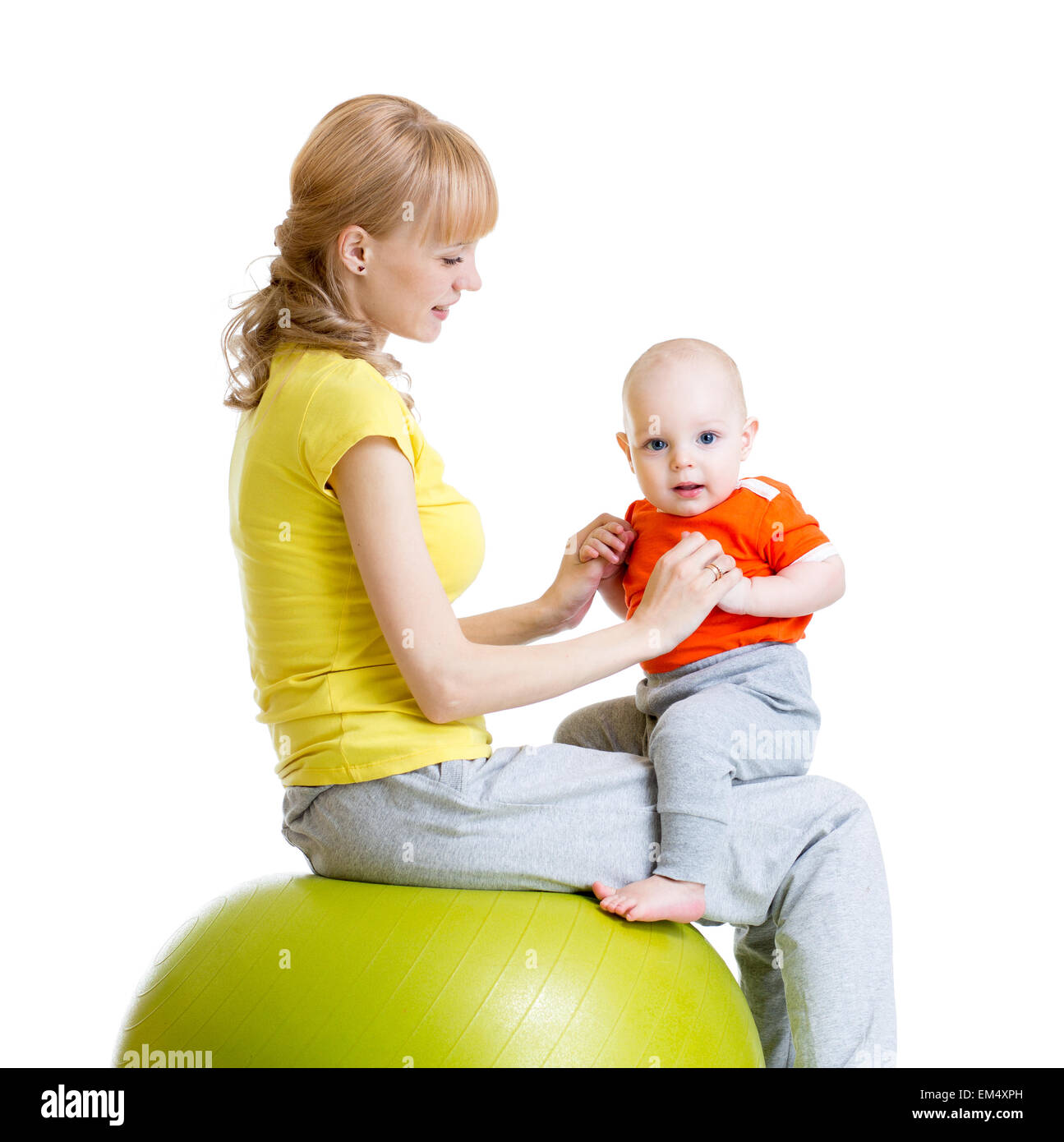 mother doing gymnastics with baby on fitness ball Stock Photo